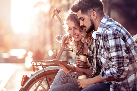 Young loving couple sitting on the park bench and having fun with tablet.Love and tenderness, lifestyle concept.