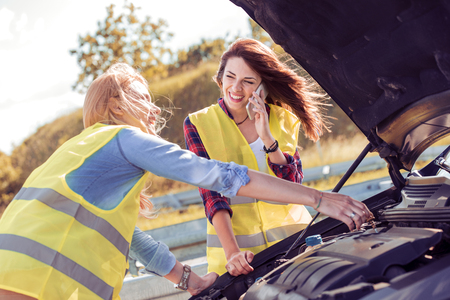 Portrait of a young girlfriends having some car trouble on a sunny day. Stock Photo
