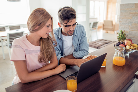 People, communication, technology and leisure.Young cute couple having breakfast while browsing on laptop.