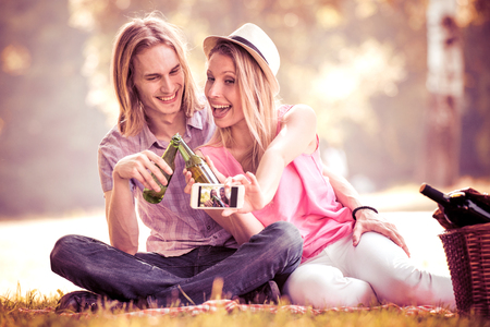 Happy couple making selfie with smart phone on picnic. Smiling caucasian couple having fun in a meadow and taking selfie.