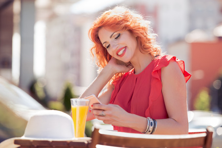 Woman in a cafe reading a text message from her mobile phone.
