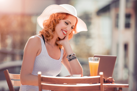 Business woman using laptop checking e-mail or message in coffee shop.