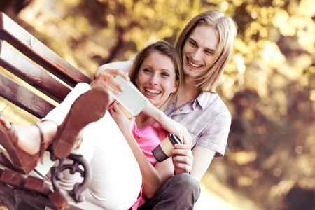 Beautiful young lover enjoy their smart phone and sitting on the bench together. Banque d'images