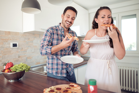 Happy couple eating pizza.Cooking together.Homemade pizza.Smiling family in the kitchen ,preparing and tasting food. Banque d'images - 120246741