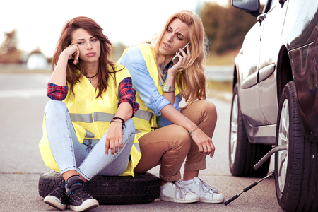Car accident woman need help and her friend call the phone to insurance broken down at the roadside. Stock Photo