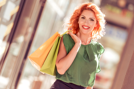 Beautiful businesswoman in town holding shopping bags and smiling.
