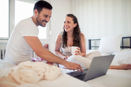 Beautiful couple spending time at home in summer morning,sitting on bed with laptop.Charming smiling girl watching movie with her boyfriend.