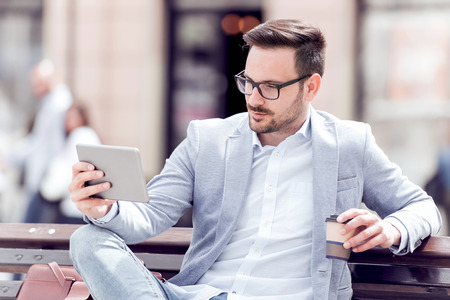Relaxed businessman using his PC tablet while sitting on a bench. Rest and drink coffee for taking.
