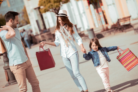 Happy parents do shopping walking with bags downtown. Stock Photo