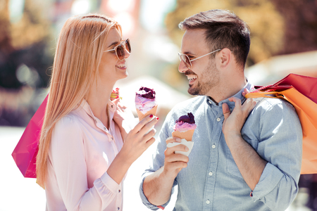 Young beautiful couple in love eating ice cream and smiling after shopping.