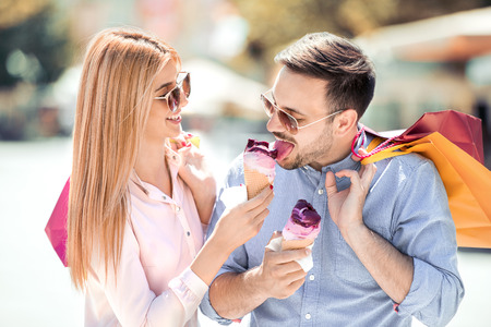 Portrait of happy young couple in the city eating ice-cream and smiling after shopping.