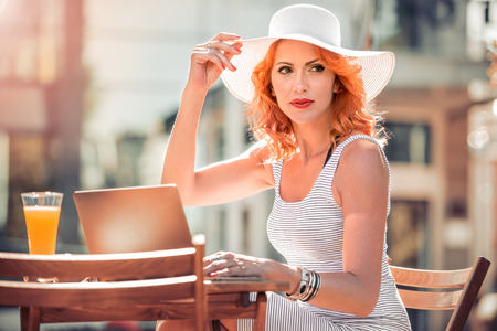Elegant businesswoman relaxing in cafe and working on a laptop computer reading information on the screen as she browses the internet. Stock Photo