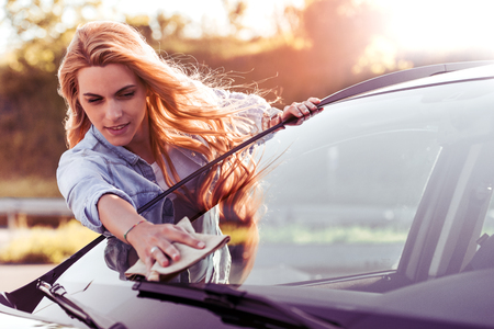 Young woman cleaning car with microfiber cloth, car detailing . Stock Photo