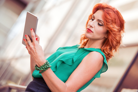 Attractive young businness woman with smart phone in the city. Stock Photo