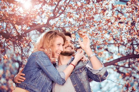 Young couple standing and hugging outdoors. Stock Photo