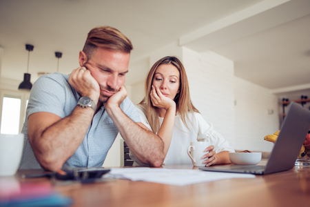 Couple having problem with bills.Worried young couple doing their accounts in the living room. 스톡 콘텐츠
