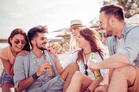 Groep vrolijke jonge mensen die op het strand ontspannen.
