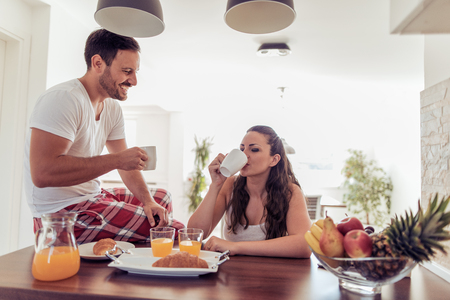 Cute young couple having breakfast together at home in their kitchen. Banque d'images - 120246774