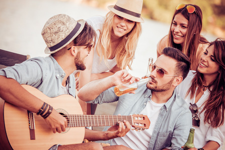 Group of friends having a party on the beach. Stock Photo