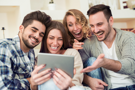 Happy young people enjoying time together,using tablet. Stock Photo