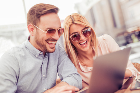 Cheerful couple using laptop outdoors,having fun outdoors.