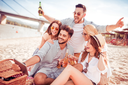 Cheerful group of friends having fun, taking selfie at sunset on the beach. Stock Photo