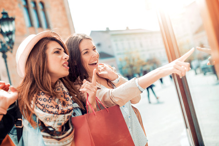 Happy woman with shopping bags pointing finger in the shop window. Stock Photo