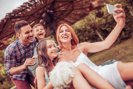 Happy family with dog taking selfie by smart phone in the park.Family, pet, technology and people concept.