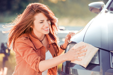 Young woman, driver, dry wiping her car with microfiber cloth after washing it, cleaning auto.