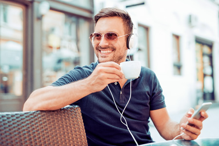 Close up of handsome young man smiling while listening to music. Stock Photo