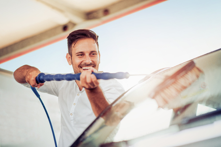 Man taking care and cleaning his car outdoors.