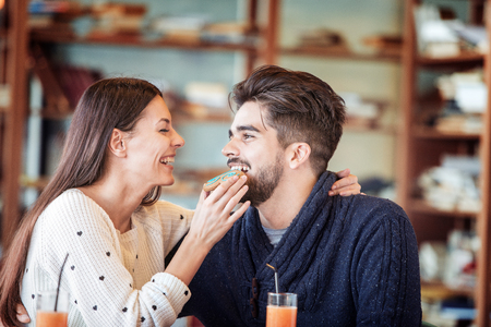 Happy young couple enjoying breakfast in a cafe. Stock Photo