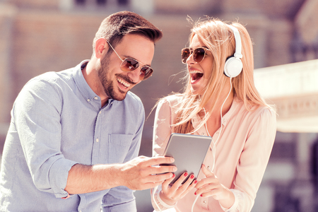 Happy couple with headphones sharing music from a tablet on the street. Stock Photo