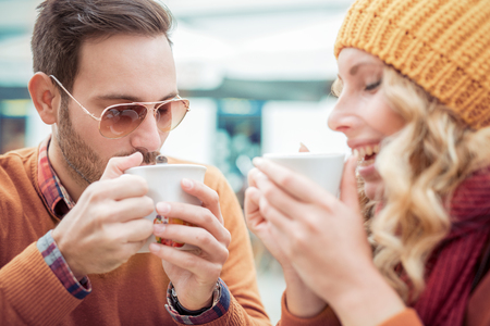 Happy couple in nature drinking tea outdoors and smiling.