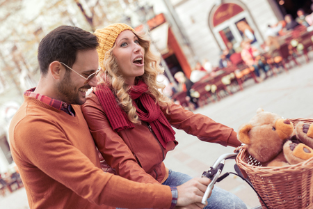 Happy couple laughing while riding bicycles in the city. Stock Photo