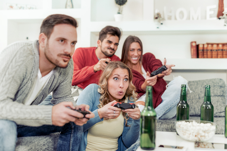 Beautiful couples playing video games on console ,having fun with beer and popcorn.