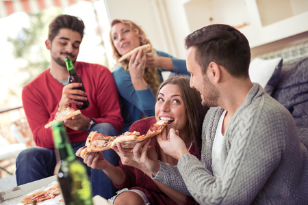 Friends with pizza and bottles of drinks having party at home.