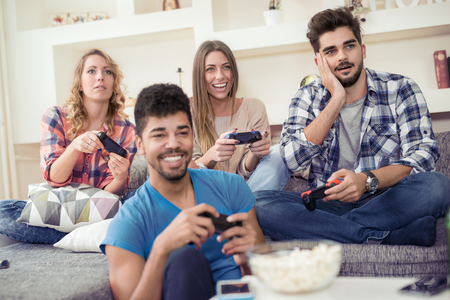 Friends having fun while playing video game in the livingroom. Stock Photo