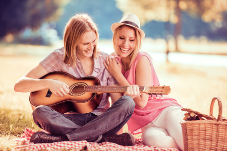 Couple in love playing guitar and singing outdoor in the park. Stock Photo