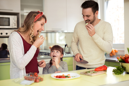 Lovely young family preparing meal in their kitchen. Stock Photo