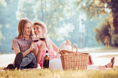 Happy young romantic couple in love having a picnic outdoor on a summer day.