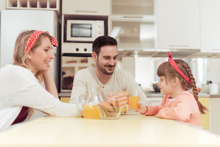 Smiling  family raising glasses together in the kitchen.
