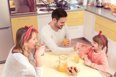 Happy family drink juice and eating cookies in the kitchen. Stock Photo