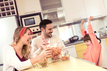 Dad, mom and their little daughter lunching together in their  kitchen.