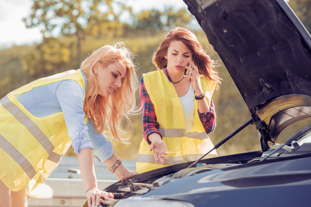 Two woman with a broken car, wait for assistance