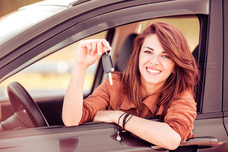 Happy woman driver showing car keys.