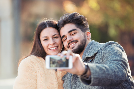 Romantic couple relaxing in the park,taking selfie.