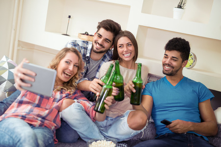 Group of attractive young people sitting on the sofa, doing selfie and smiling.