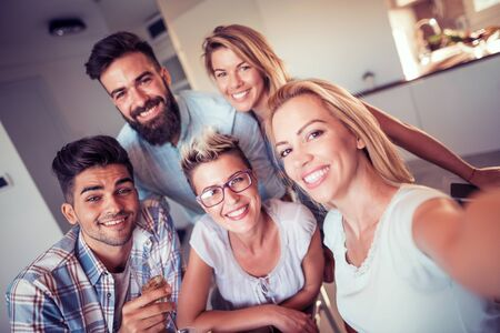 Happy young friends taking selfie with smart phone at home.