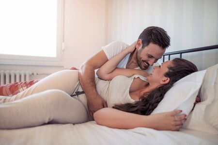 Loving couple lying on bed.Man and woman enjoy time together.
